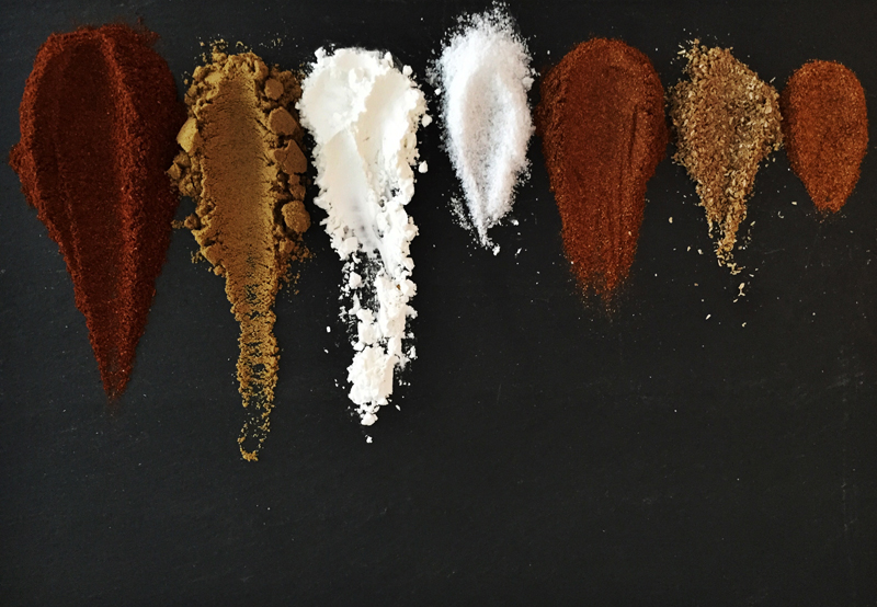 Homemade taco seasoning ingredients lined up on a black cutting board.