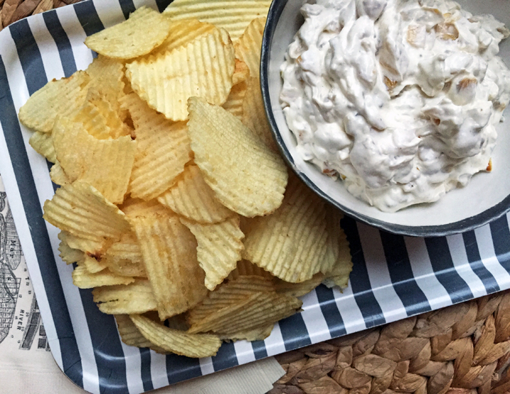 Onion dip in a bowl on top of a striped platter with ruffled potato chips.