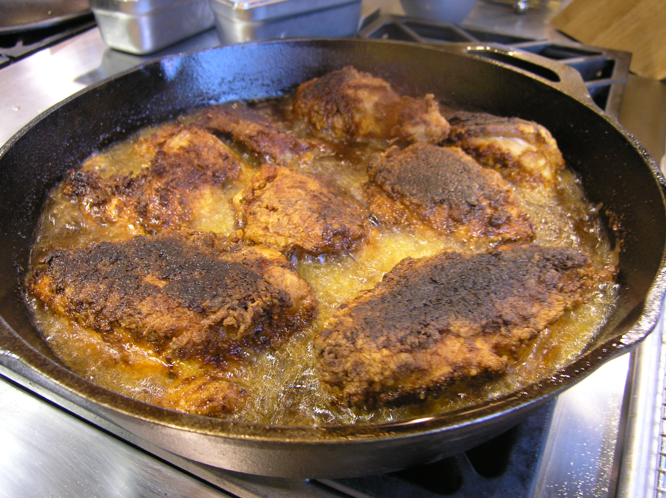 Fried chicken frying in a cast-iron skillet on the set of Alton Brown's Good Eats.