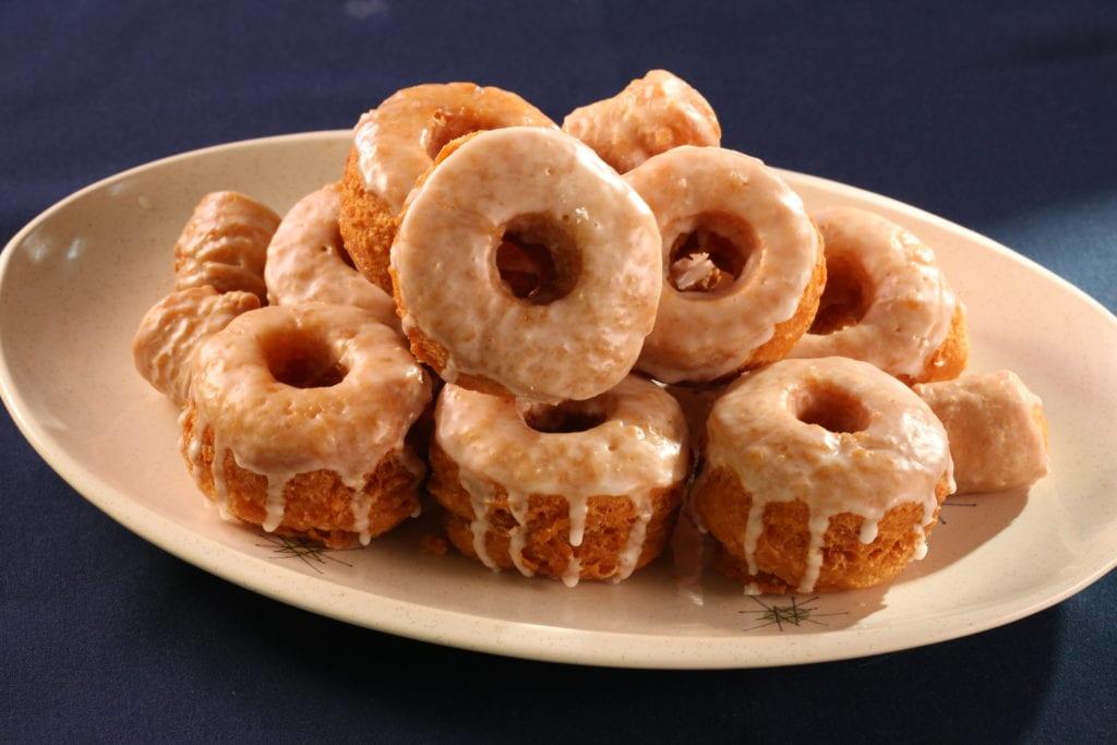 Hot glazed bonuts piled on a white serving platter.
