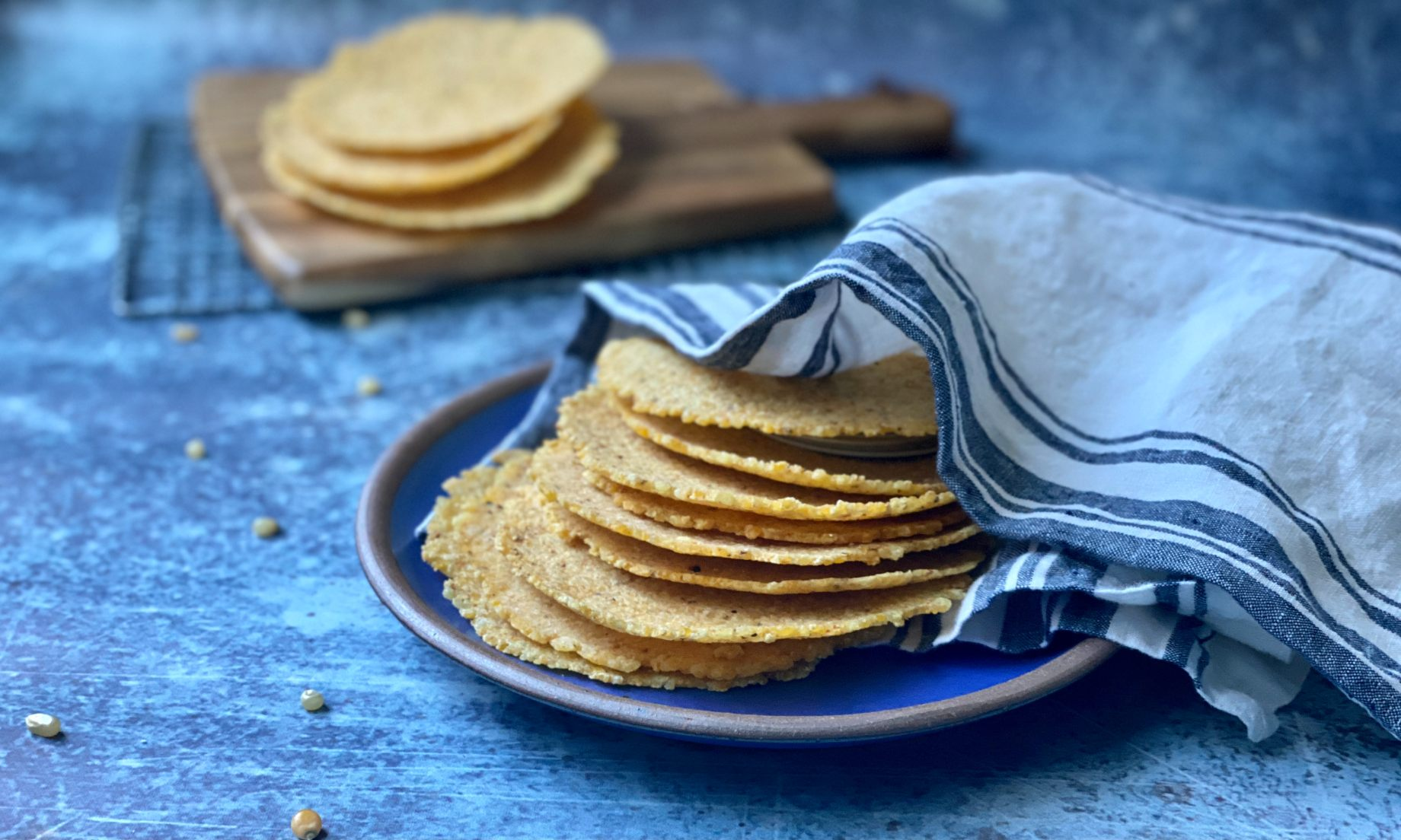 Corn tortillas stacked on a blue plate and wrapped in a kitchen towel.