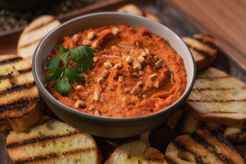 Smoky romesco sauce in a grey bowl surrounded by pieces of grilled, toasted baguette.