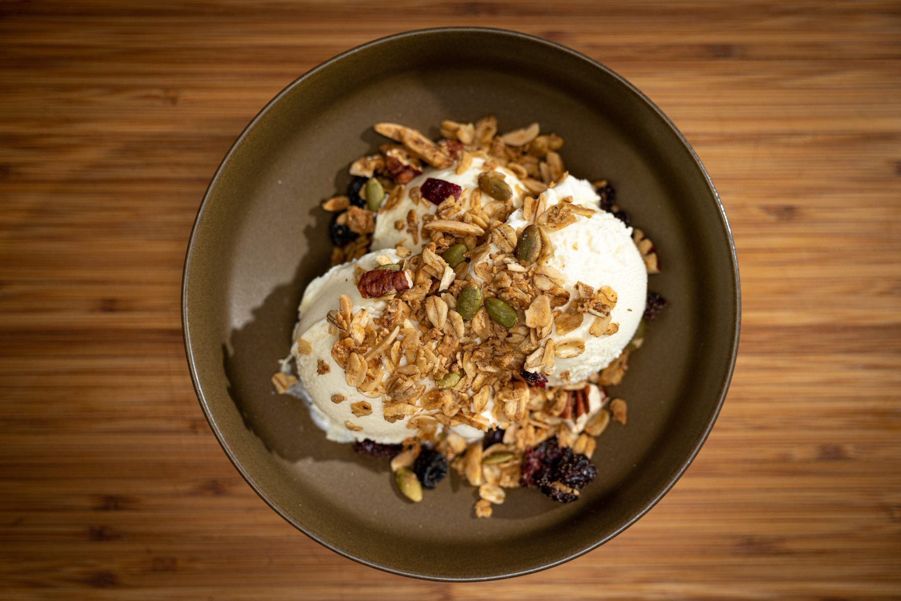 Reloaded granola sprinkled on top of vanilla ice cream in a brown bowl.