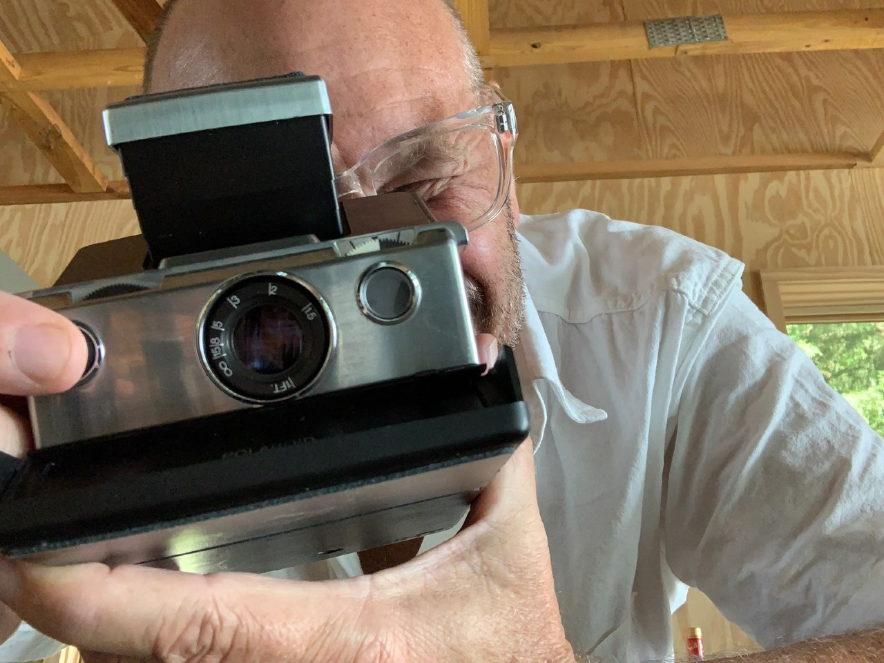 Alton Brown holding old fashioned camera
