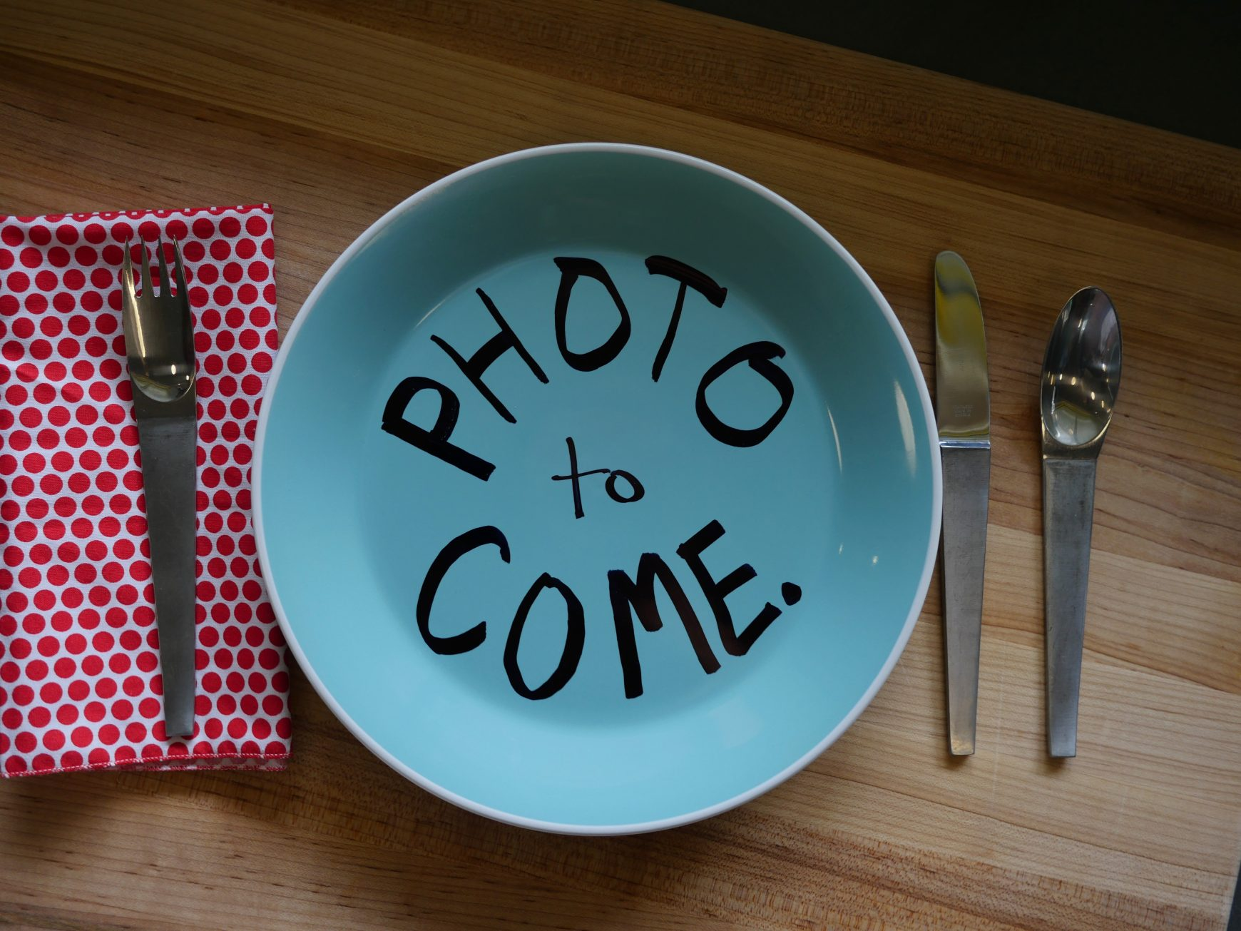 "A blue plate with the words ""Photo to Come"" written in black marker flanked by Alton Brown's vintage silverware."