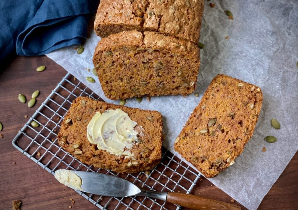 Cinnamon pumpkin bread slices on a parchment paper-lined cooling rack
