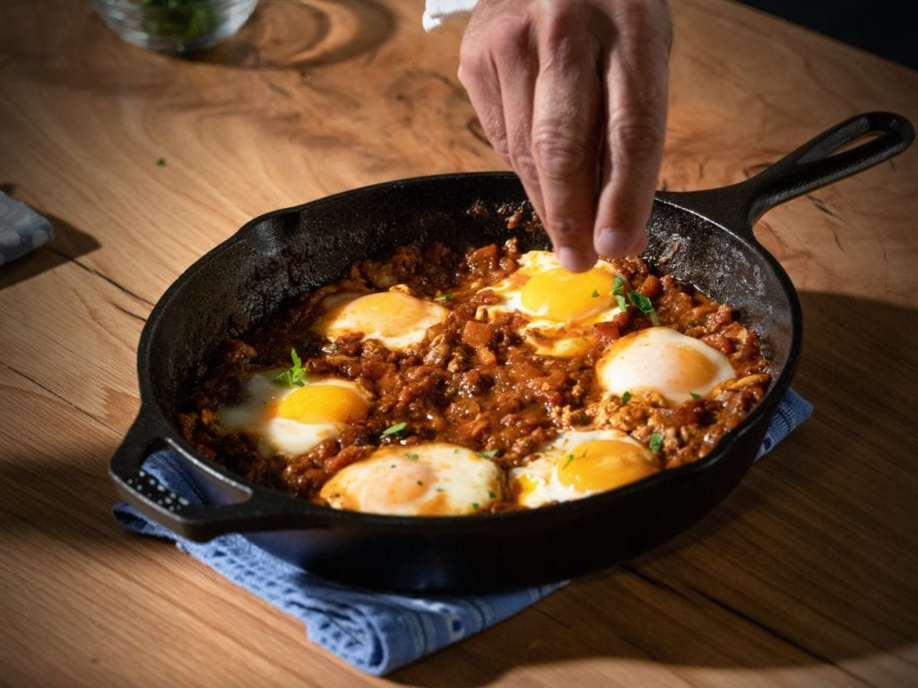 Red Shakshuka with six poached eggs in a large cast-iron skillet.