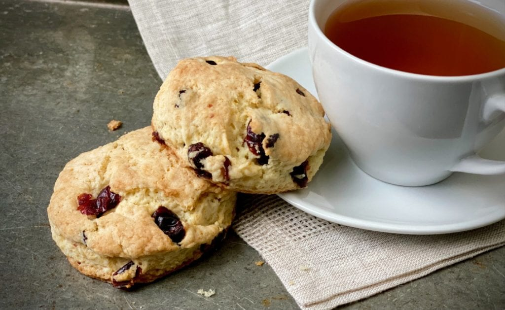 Scones from scratch on a kitchen towel next to a cup of tea.