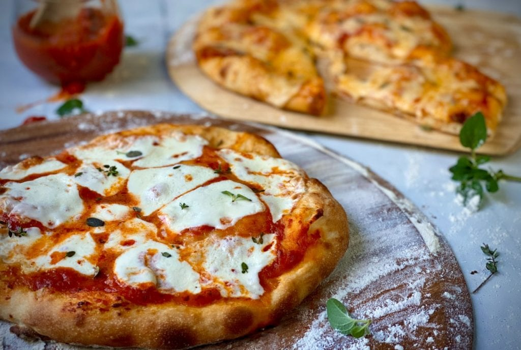 Pizza pizzas cooling on pizza stone.