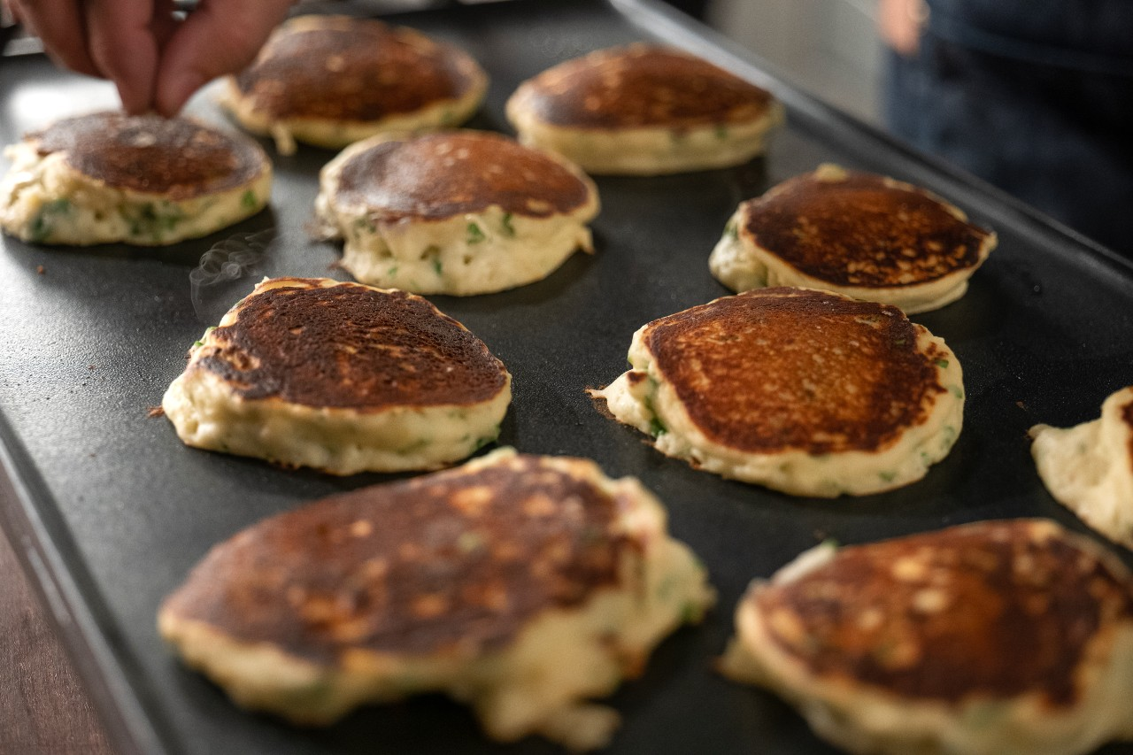 Ricotta latkes cooking on griddle